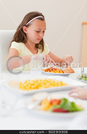 Girl eating at dinner table stock photo, Girl eating at the dinner table by Wavebreak Media