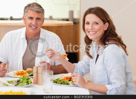 Smiling couple eating dinner stock photo, Smiling couple eating dinner together by Wavebreak Media