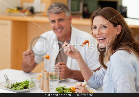 Laughing couple eating dinner stock photo, Laughing couple eating dinner together by Wavebreak Media