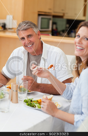 Happy couple eating their dinner stock photo, Happy couple eating their dinner together by Wavebreak Media