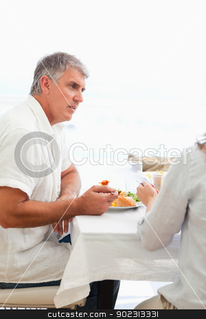 Side view of man having dinner stock photo, Side view of mature man having dinner by Wavebreak Media
