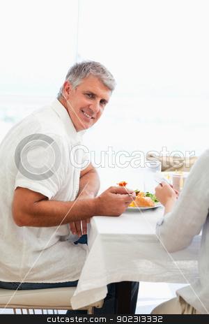 Side view of smiling man having dinner stock photo, Side view of smiling mature man having dinner by Wavebreak Media