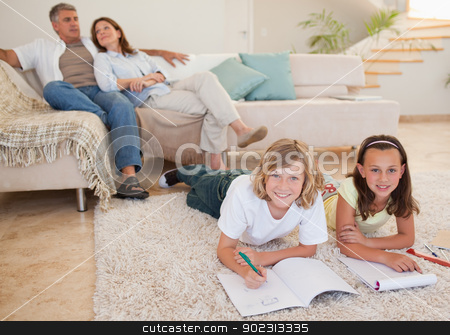 Siblings doing homework on the carpet with parents behind them stock photo, Siblings doing their homework on the carpet with parents behind them by Wavebreak Media