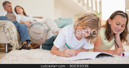 Siblings doing their homework on the carpet with parents behind  stock photo, Siblings doing their homework on the carpet with their parents behind them by Wavebreak Media