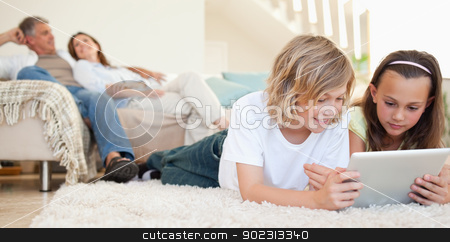 Siblings with tablet on the floor stock photo, Siblings with tablet lying on the floor by Wavebreak Media