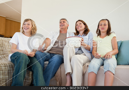Family on the couch watching tv stock photo, Family on the couch watching tv together by Wavebreak Media