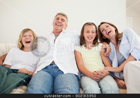 Laughing family sitting on the sofa stock photo, Laughing family sitting on the sofa together by Wavebreak Media