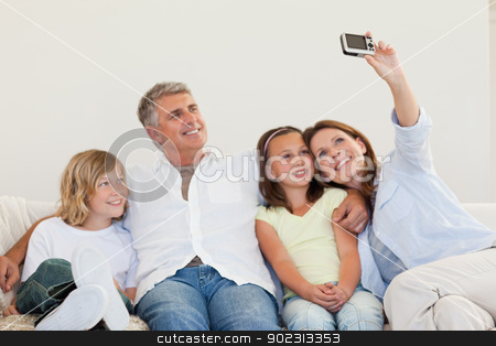 Mother taking a picture on the sofa stock photo, Mother taking a family picture on the sofa by Wavebreak Media