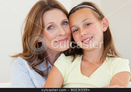 Mother hugging her daughter stock photo, Smiling mother hugging her daughter by Wavebreak Media