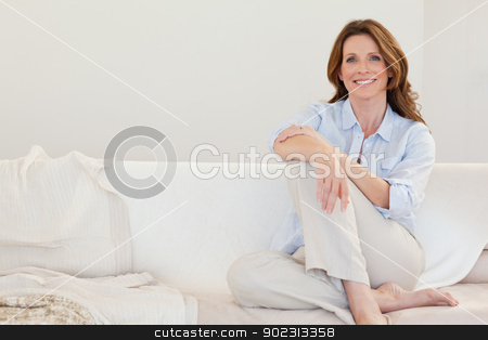 Smiling mature woman sitting on sofa stock photo, Smiling mature woman sitting on her sofa by Wavebreak Media