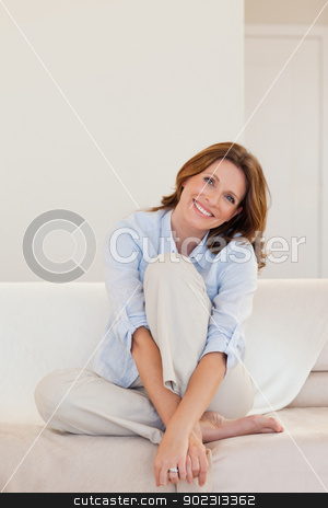 Smiling mature woman sitting on couch stock photo, Smiling mature woman sitting on her couch by Wavebreak Media