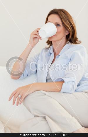 Woman drinking coffee on sofa stock photo, Woman drinking coffee on her sofa by Wavebreak Media