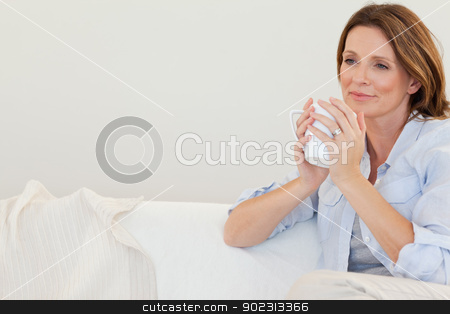Thoughtful woman with cup of coffee on sofa stock photo, Thoughtful woman with cup of coffee on the sofa by Wavebreak Media