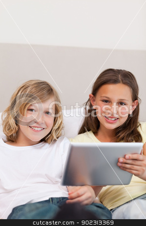 Brother and sister using tablet on couch stock photo, Brother and sister using tablet on the couch by Wavebreak Media