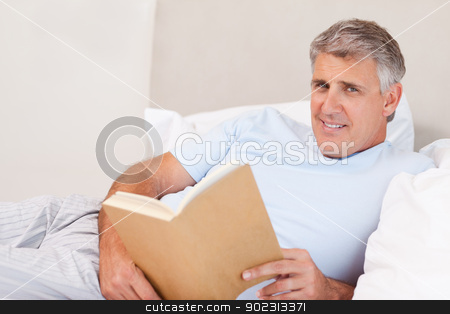 Smiling man with book in bed stock photo, Smiling man with book in the bed by Wavebreak Media
