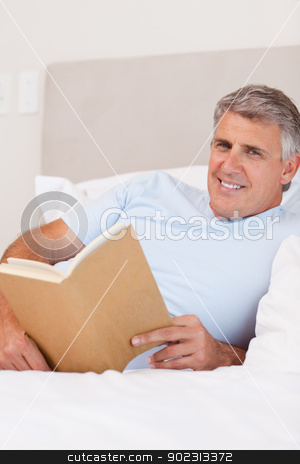 Smiling man reading in bed stock photo, Smiling man reading in the bed by Wavebreak Media
