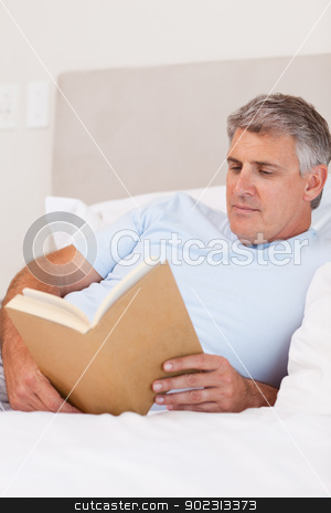 Man reading book in bed stock photo, Man reading book in his bed by Wavebreak Media