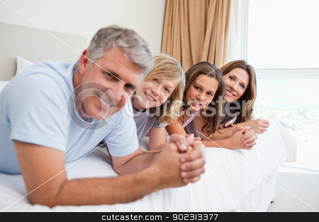 Happy family lying on the bed stock photo, Happy family lying on the bed together by Wavebreak Media