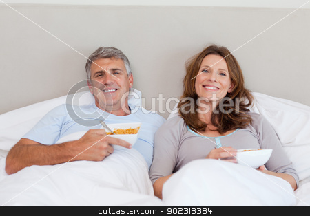 Couple eating cereals in bed stock photo, Mature couple eating cereals in bed by Wavebreak Media