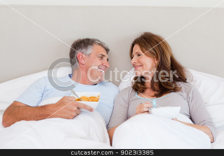 Happy couple eating cereals in bed stock photo, Happy mature couple eating cereals in bed by Wavebreak Media
