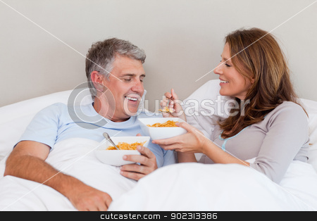 Mature couple having breakfast in bed stock photo, Mature couple having breakfast in their bed by Wavebreak Media