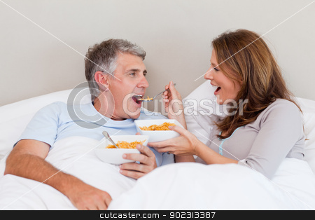 Mature couple eating cereals in bed stock photo, Mature couple eating cereals in their bed by Wavebreak Media
