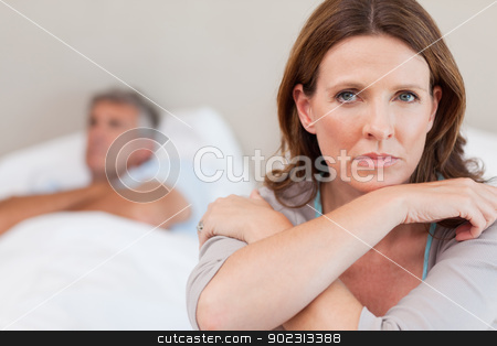 Sad woman on the bed with husband in background stock photo, Sad woman on the bed with her husband in the background by Wavebreak Media