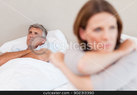 Sad man in bed with his wife in the foreground stock photo, Sad man in the bed with his wife in the foreground by Wavebreak Media
