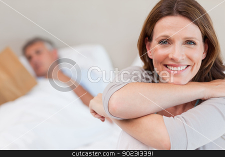 Smiling woman on bed with reading husband in the background stock photo, Smiling woman on the bed with reading husband in the background by Wavebreak Media