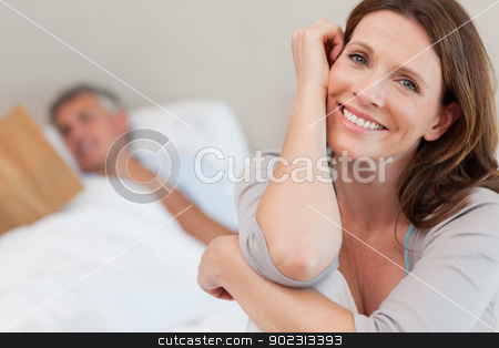Happy smiling woman on bed with husband reading behind her stock photo, Happy smiling woman on the bed with husband reading behind her by Wavebreak Media