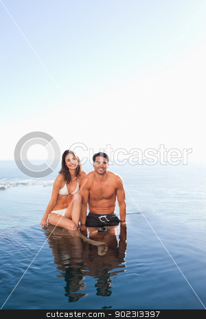 Couple sitting on pool edge with sea in the background stock photo, Couple sitting on the pool edge with sea in the background by Wavebreak Media