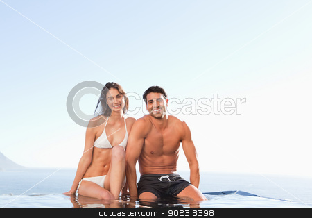 Smiling couple sitting on pool edge stock photo, Smiling couple sitting on the pool edge by Wavebreak Media