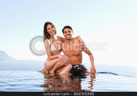 Happy couple sitting on pool edge stock photo, Happy couple sitting on the pool edge by Wavebreak Media