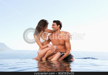 Couple sitting on pool edge together stock photo, Couple sitting on the pool edge together by Wavebreak Media