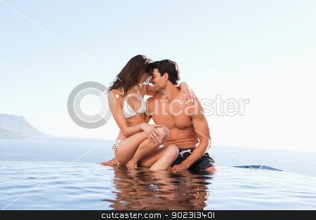 Couple on the pool edge stock photo, Couple on the pool edge together by Wavebreak Media