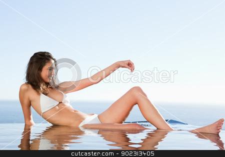 Woman sunbathing on pool edge stock photo, Woman sunbathing on the pool edge by Wavebreak Media