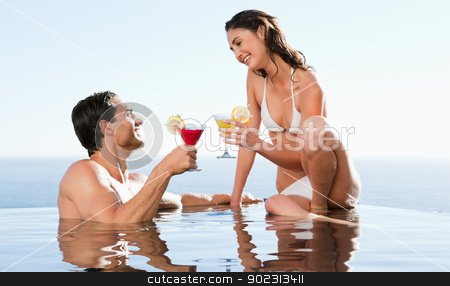 Couple having cocktails in the pool stock photo, Happy couple having cocktails in the pool by Wavebreak Media