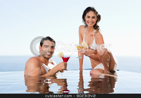 Cheerful couple having cocktails in the pool stock photo, Cheerful young couple having cocktails in the pool by Wavebreak Media