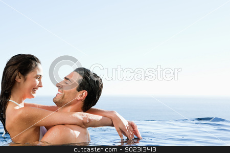 Couple embracing in the pool stock photo, Young couple embracing in the pool by Wavebreak Media