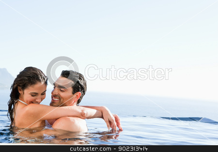 Couple hugging in the pool stock photo, Young couple hugging in the pool by Wavebreak Media