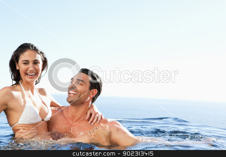 Couple enjoying time together in the pool stock photo, Couple enjoying their time together in the pool by Wavebreak Media