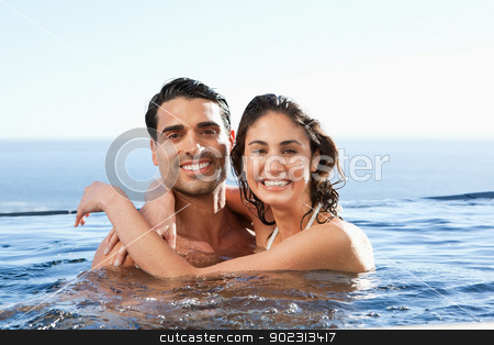 Smiling couple embracing in the pool stock photo, Smiling young couple embracing in the pool by Wavebreak Media