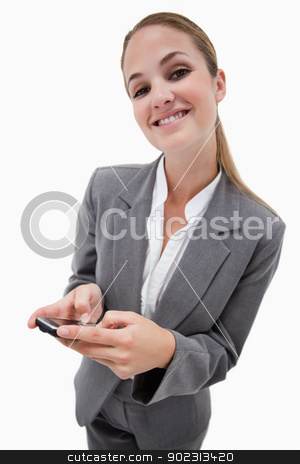 Portrait of a smiling businesswoman using a smartphone stock photo, Portrait of a smiling businesswoman using a smartphone against a white background by Wavebreak Media