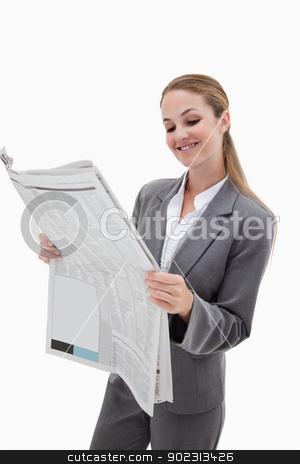Portrait of a smiling businesswoman reading the news stock photo, Portrait of a smiling businesswoman reading the news against a white background by Wavebreak Media