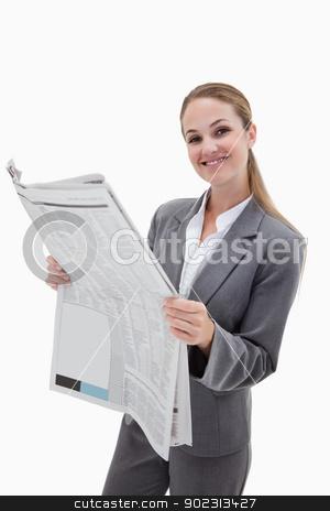 Portrait of a happy businesswoman reading the news stock photo, Portrait of a happy businesswoman reading the news against a white background by Wavebreak Media