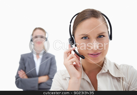Beautiful operators with headsets stock photo, Beautiful operators with headsets against a white background by Wavebreak Media