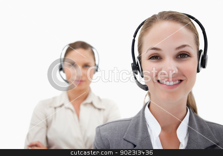 Smiling operators with headsets stock photo, Smiling operators with headsets against a white background by Wavebreak Media