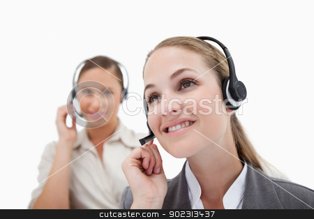 Smiling operators using headsets stock photo, Smiling operators using headsets against a white background by Wavebreak Media