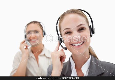 Happy operators using headsets stock photo, Happy operators using headsets against a white background by Wavebreak Media