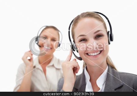 Joyful operators using headsets stock photo, Joyful operators using headsets against a white background by Wavebreak Media